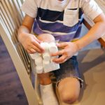 Boy holds a bag of frozen marshmallows on his bruised knee.