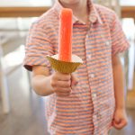 Boy holds a popsicle with a cupcake liner to catch drips.