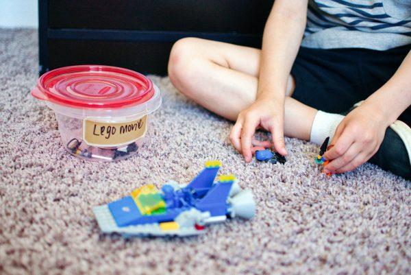 Boy plays with Legos on floor.