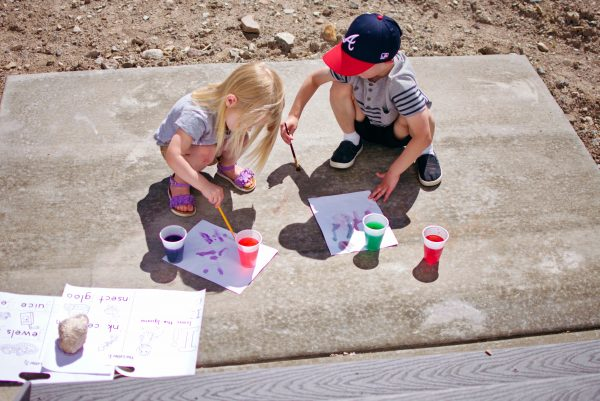 Using water cups with food coloring is a great mom hack for outside play.