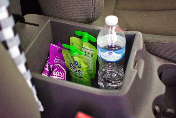 Keeping snacks in the arm rest is a great mom hack for the car.