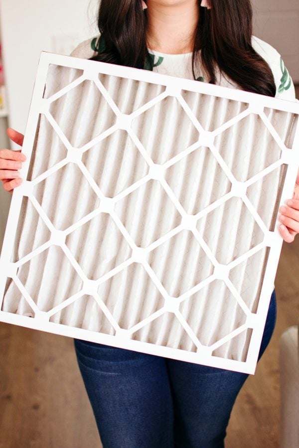 Woman holds air filter, one of her new homeowner necessities
