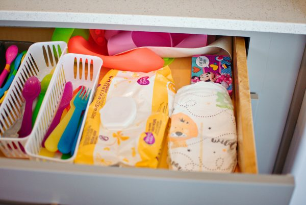 Kitchen drawer with diapers and wipes.