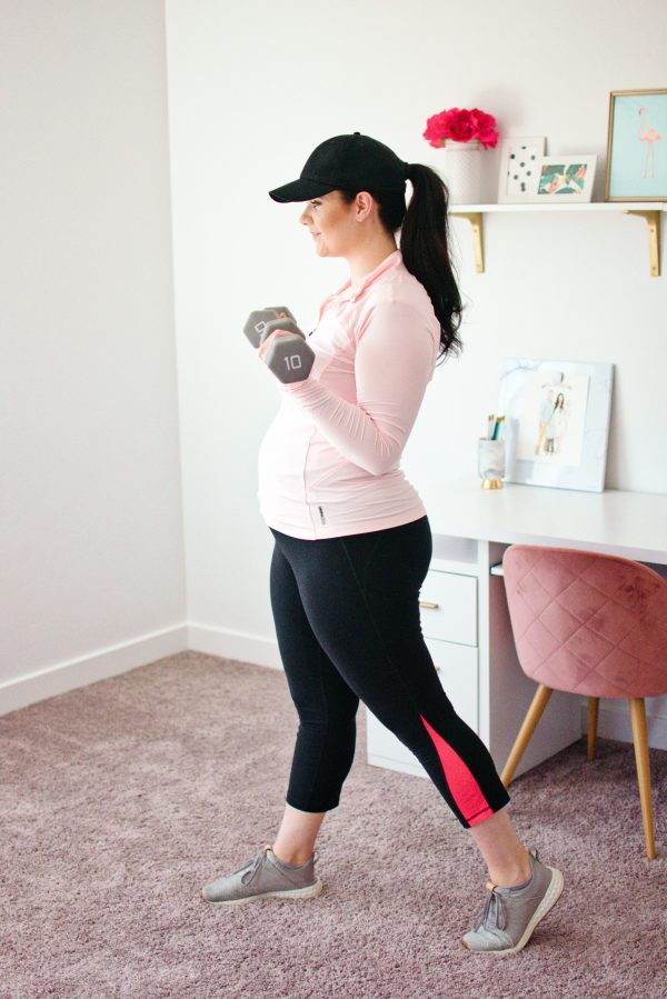 Woman lifts weights as part of her pregnancy workout routine.