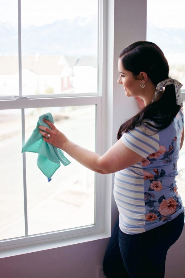 Mom cleans the windows as part of her realistic cleaning schedule.