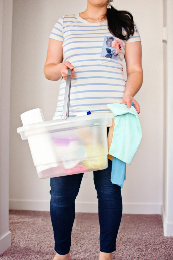 Woman holds cleaning bucket and cloths.