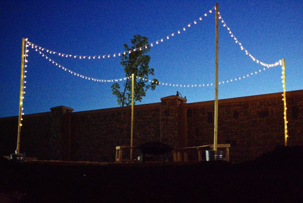 Amazon backyard lights strung on DIY light poles.