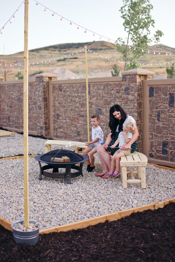 A mom and her two kids sit around their backyard fire pit.