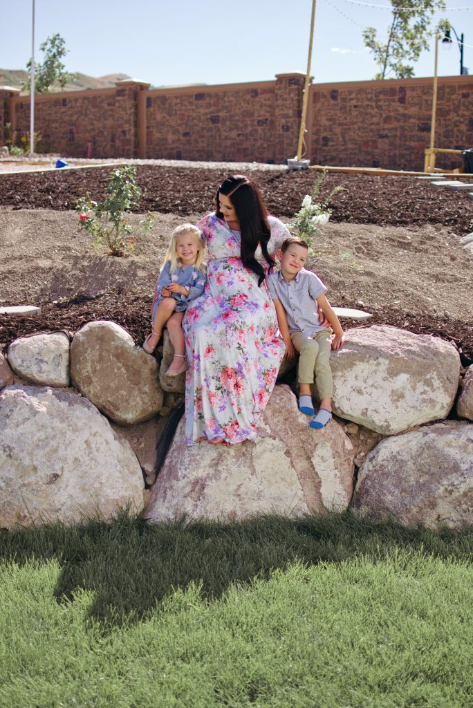 A mom sits with her two children for backyard landscaping pictures.