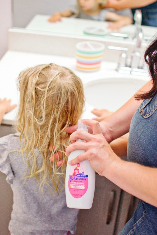 A mom shares hair tips and sprays Johnsons leave in conditioner for kids in her daughter's hair.