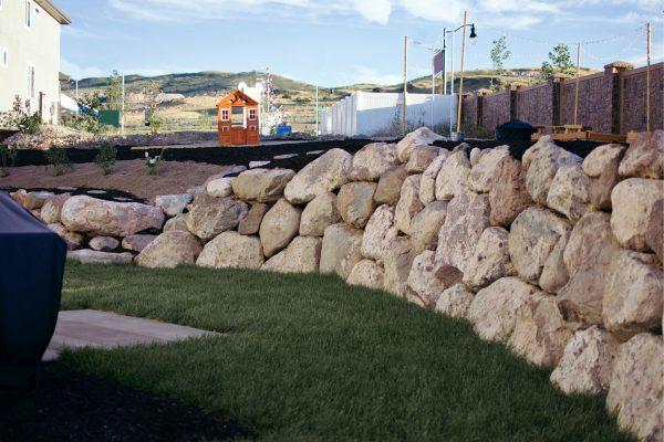 Pinterest backyard ideas featuring a rockwall and mulch.
