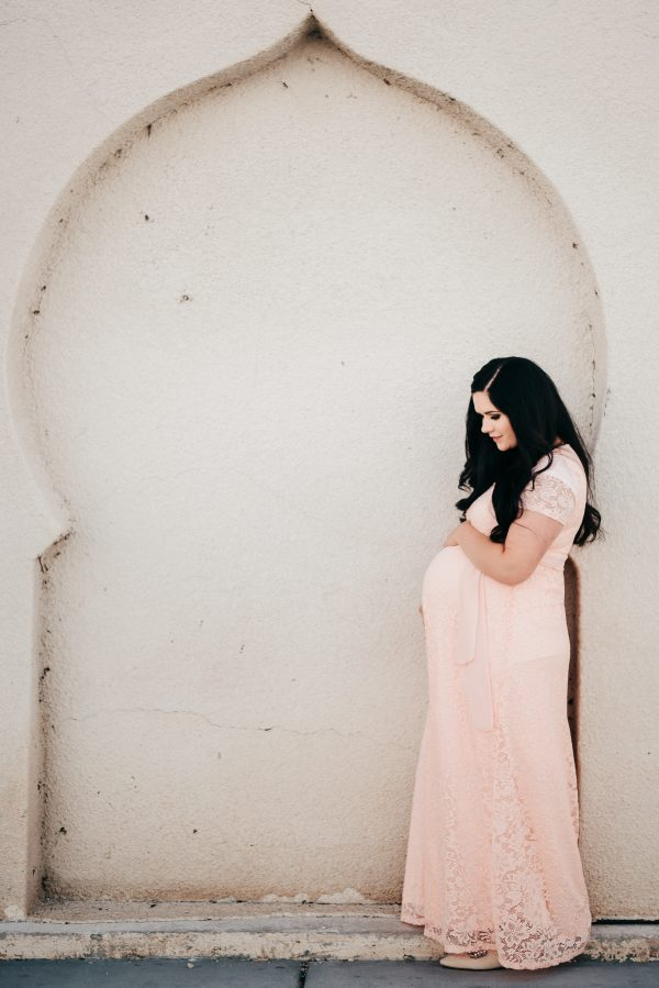 Woman wears a pink dress for her maternity pictures outfit.