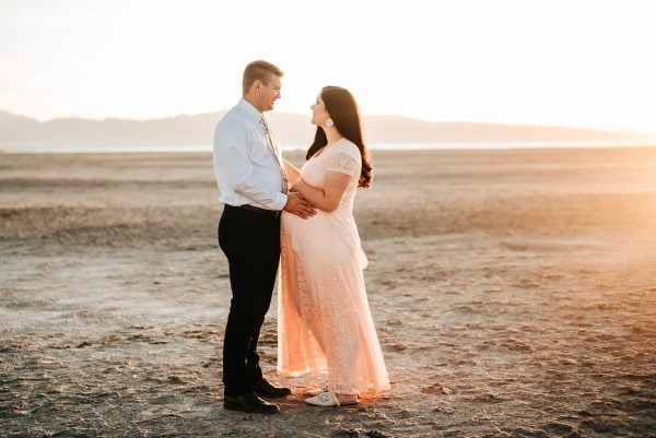 Couple poses for outdoor maternity photography.