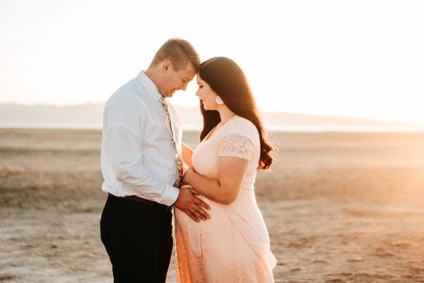 Woman takes maternity pictures with husband.