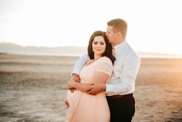 Couple poses for beach maternity pictures.