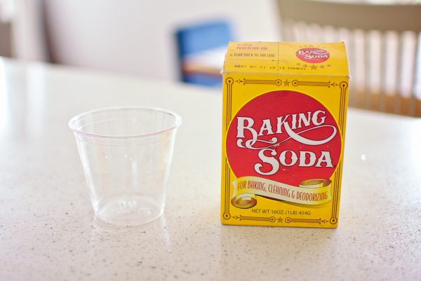 Baking soda and cup on kitchen counter for gender predictor test.