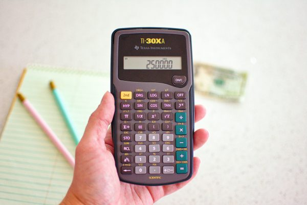 Woman holds a refinance calculator to determine when to refinance a home