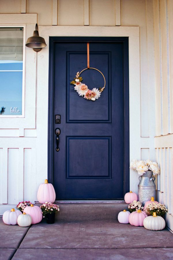 Front porch with blue door, fall wreath, painted pink pumpkins, and containers of mums.