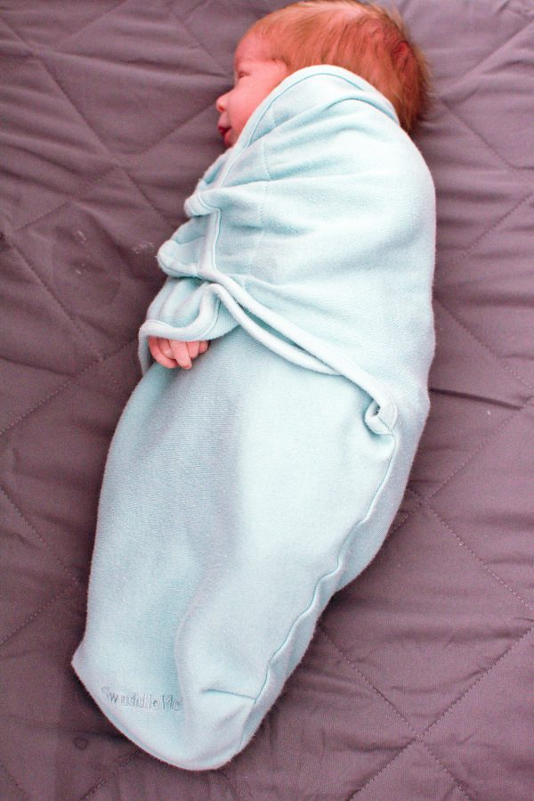 Newborn baby in a velcro swaddle.