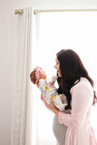 New mom with postpartum body holding baby.