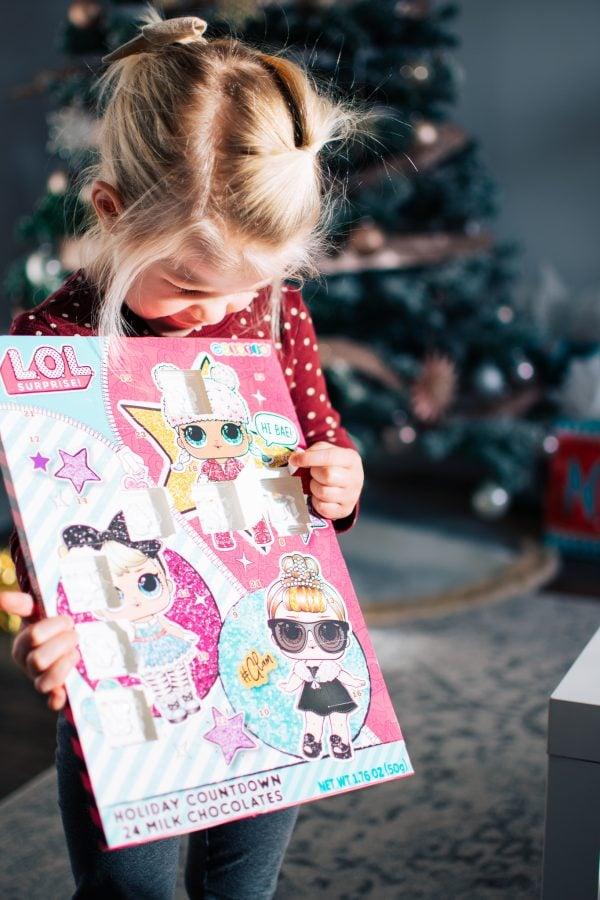 Little girl holds advent calendar as a family Christmas tradition.