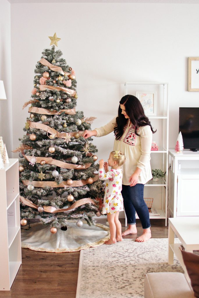 Mom and daughter decorate a Christmas tree as part of their family tradition.