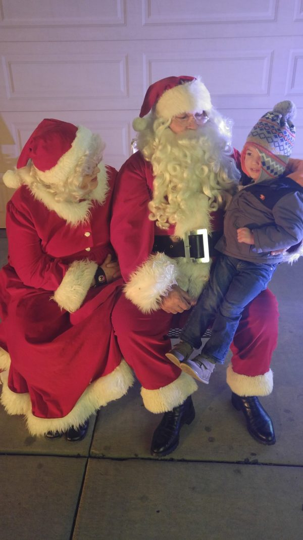 Little boy takes a Santa picture as a family Christmas tradition.