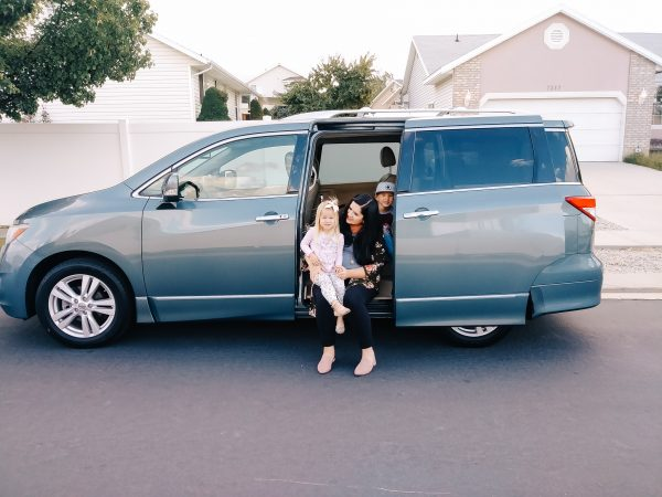 Mom sits in a car she bought with frugal living tips.