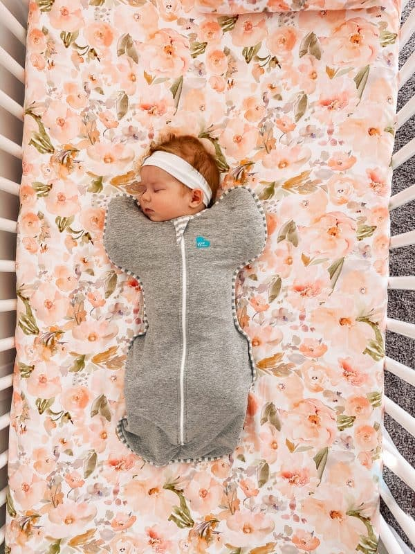Baby wears a zipper swaddle; one of the essential newborn items.