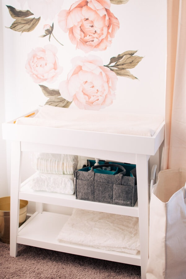White changing table in front of flower wall decals.
