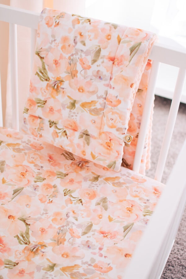 Peach and floral baby girl crib bedding.