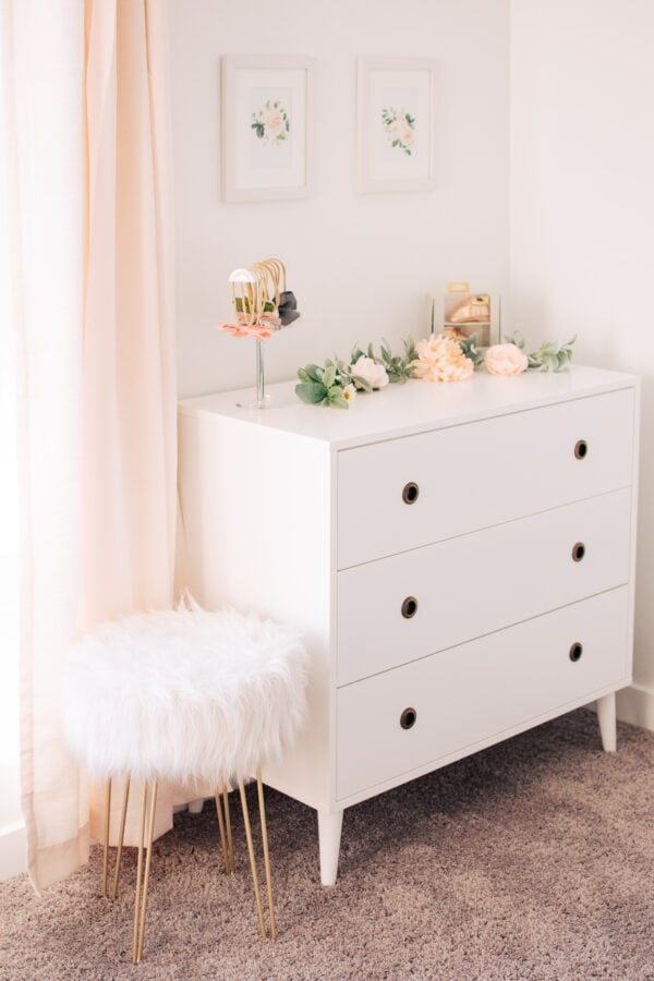Faux fur stool placed next to white dresser with floral decor.