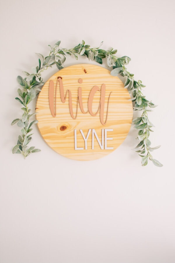 Wooden name sign hangs as part of some baby room decor.