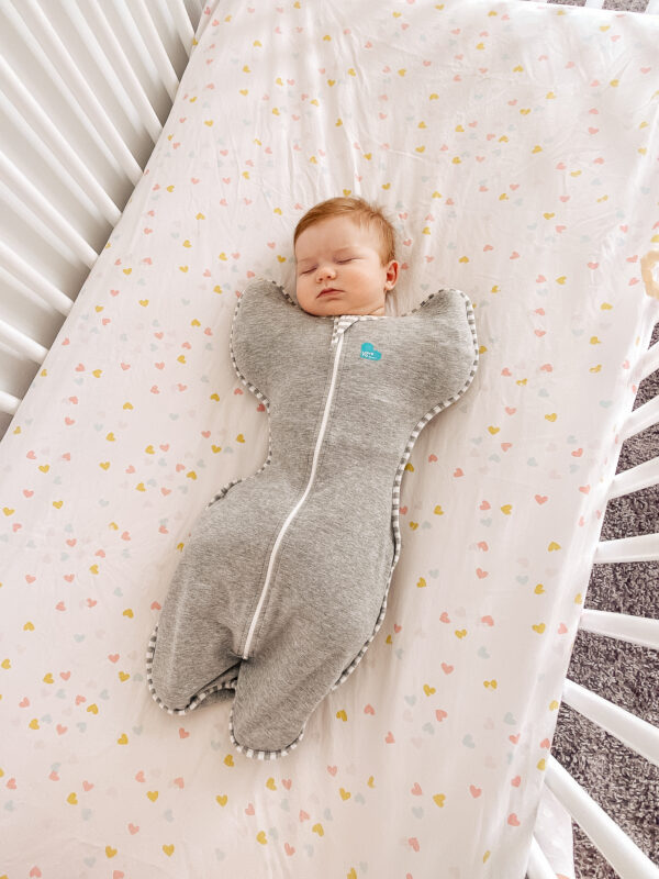 A newborn sleeps in a zipper swaddle.