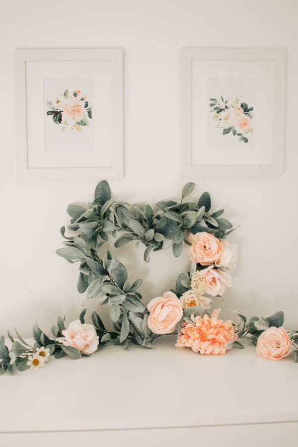 A beautiful heart shaped wreath sits on a dresser.