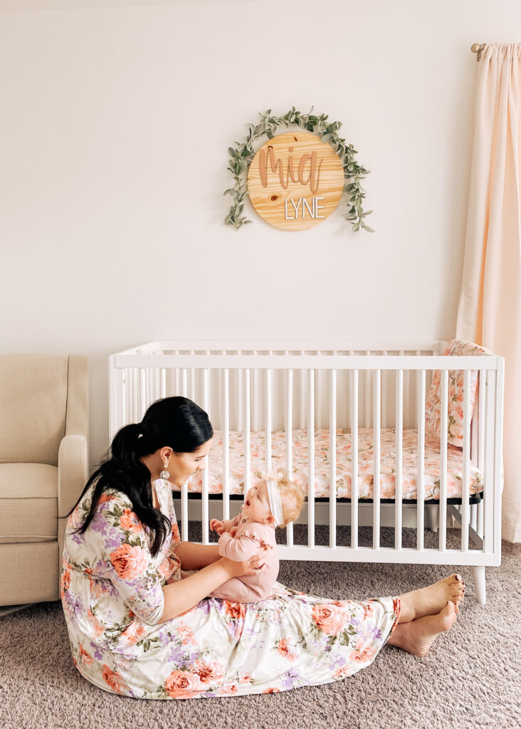 Mom holds baby girl in front of her crib and name sign.