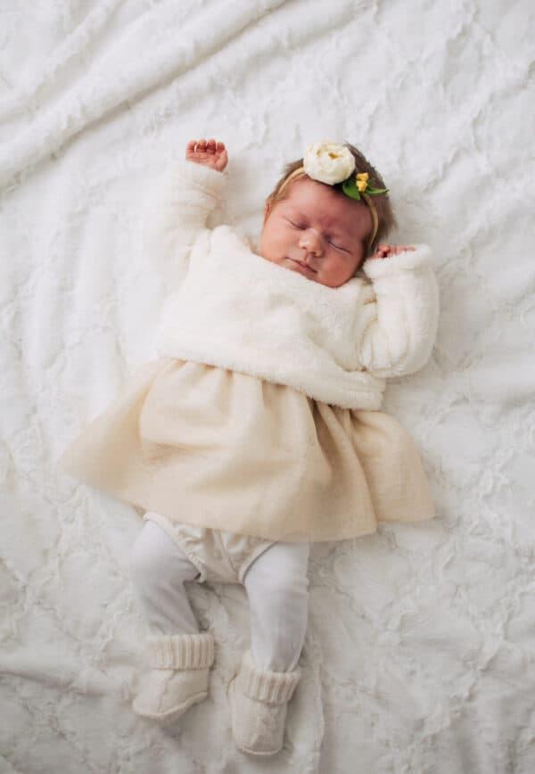 A newborn baby girl sleeps on a white blanket.