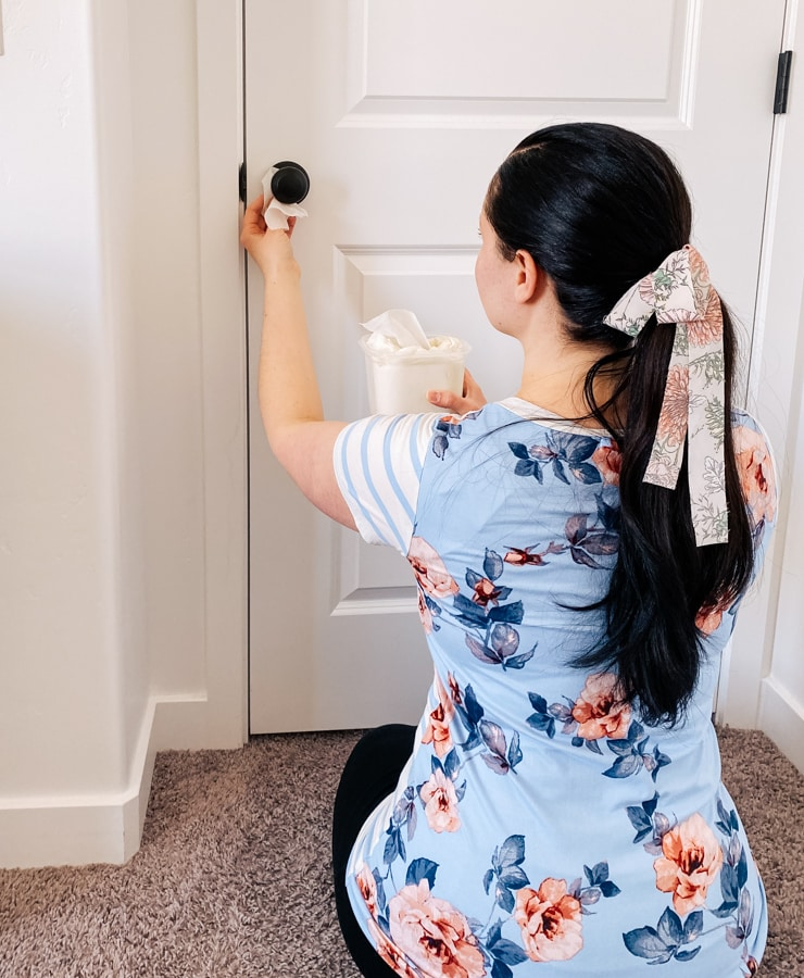 Woman cleans door knob with DIY cleaning wipes.