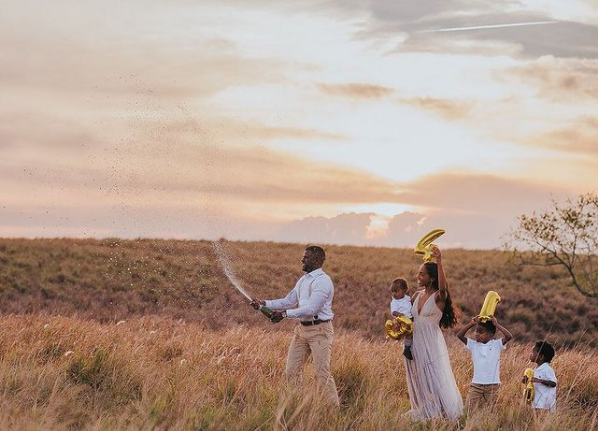 Family walks through a grassy area holding number balloons.