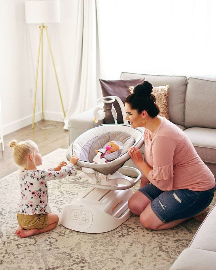 Mom and daughter play with baby swing.