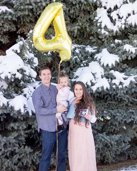 Family stands by each other and holds a number balloon.