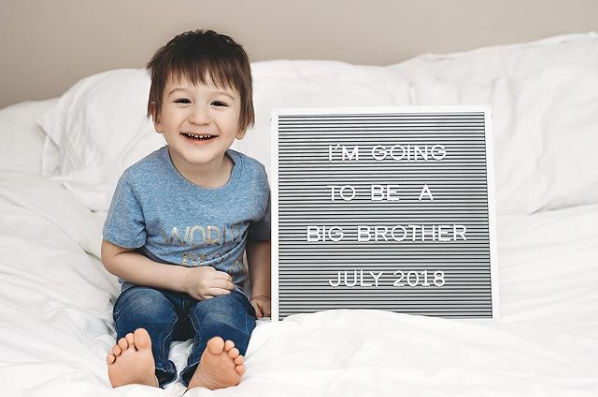 Little boy sits on baby with letter board baby annoucement.