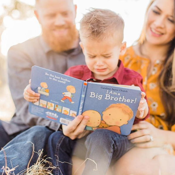 Little boy sits on his mom and dad's lap and holds a book about becoming a big brother.