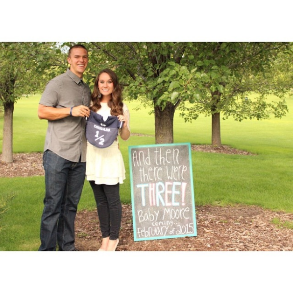 Husband and wife stand next to a chalkboard and hold a baby jersey.