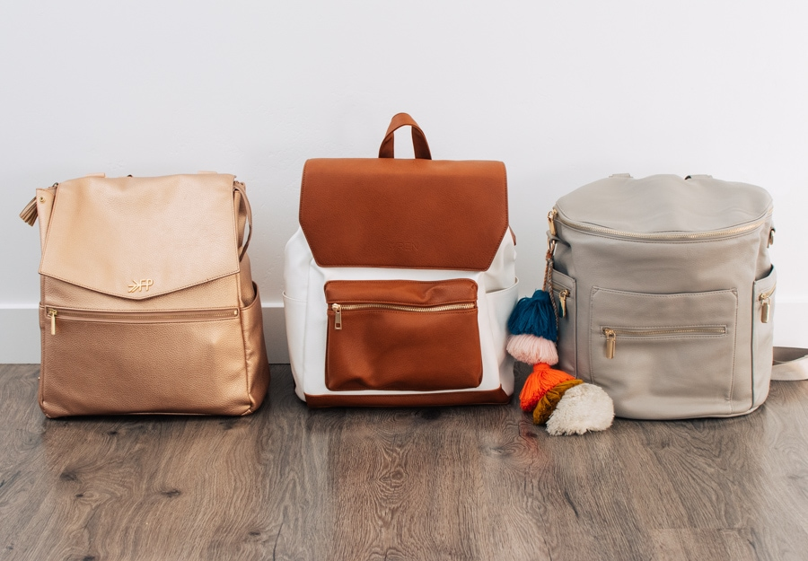 Three diaper bags lined in a row.