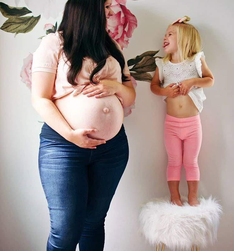 Pregnant woman shows her baby belly.
