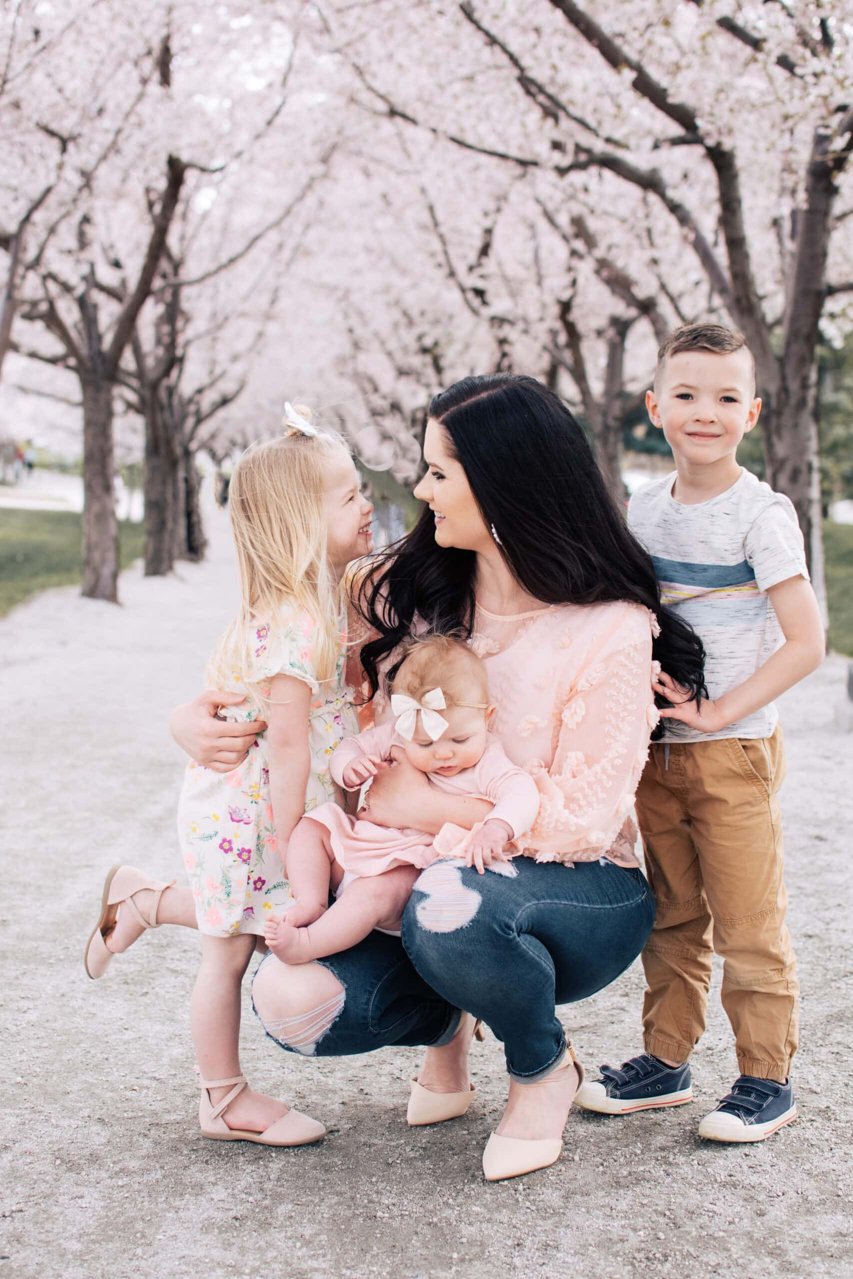 Jessica Ashcroft stands with her three kids by blossoms.
