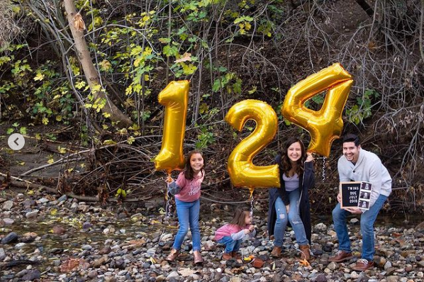 Family holds number balloons in a forest.