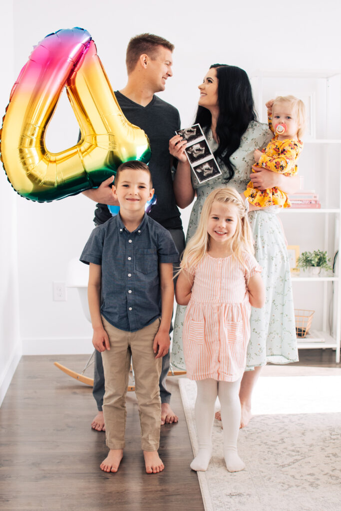 Family holds rainbow 4 balloon and ultrasound photo for pregnancy announcement.