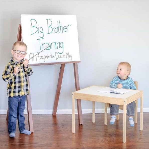 One brother stands by a flip chart and the other sits at a kids table.